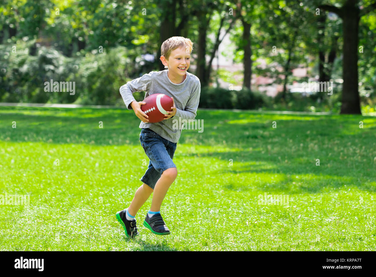 Boy Running With Rugby Ball - Stock Image