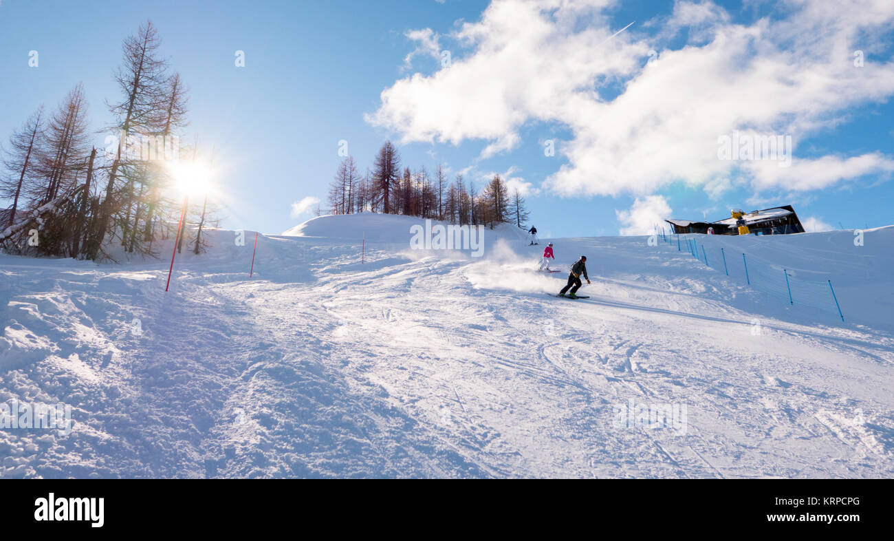 Skiers skiing downhill on mountain sunny landscape in Sauze D'Oulx Piedmont Italy - Stock Image