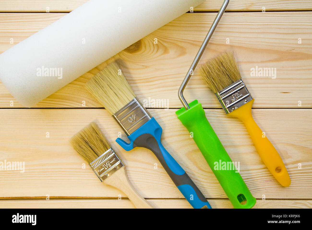 Ready To Pait A HouseA Set Of Paint Brushes And Roller For Repair On Light Uncolored Wooden Background Close Up Top View Space Your Text Or