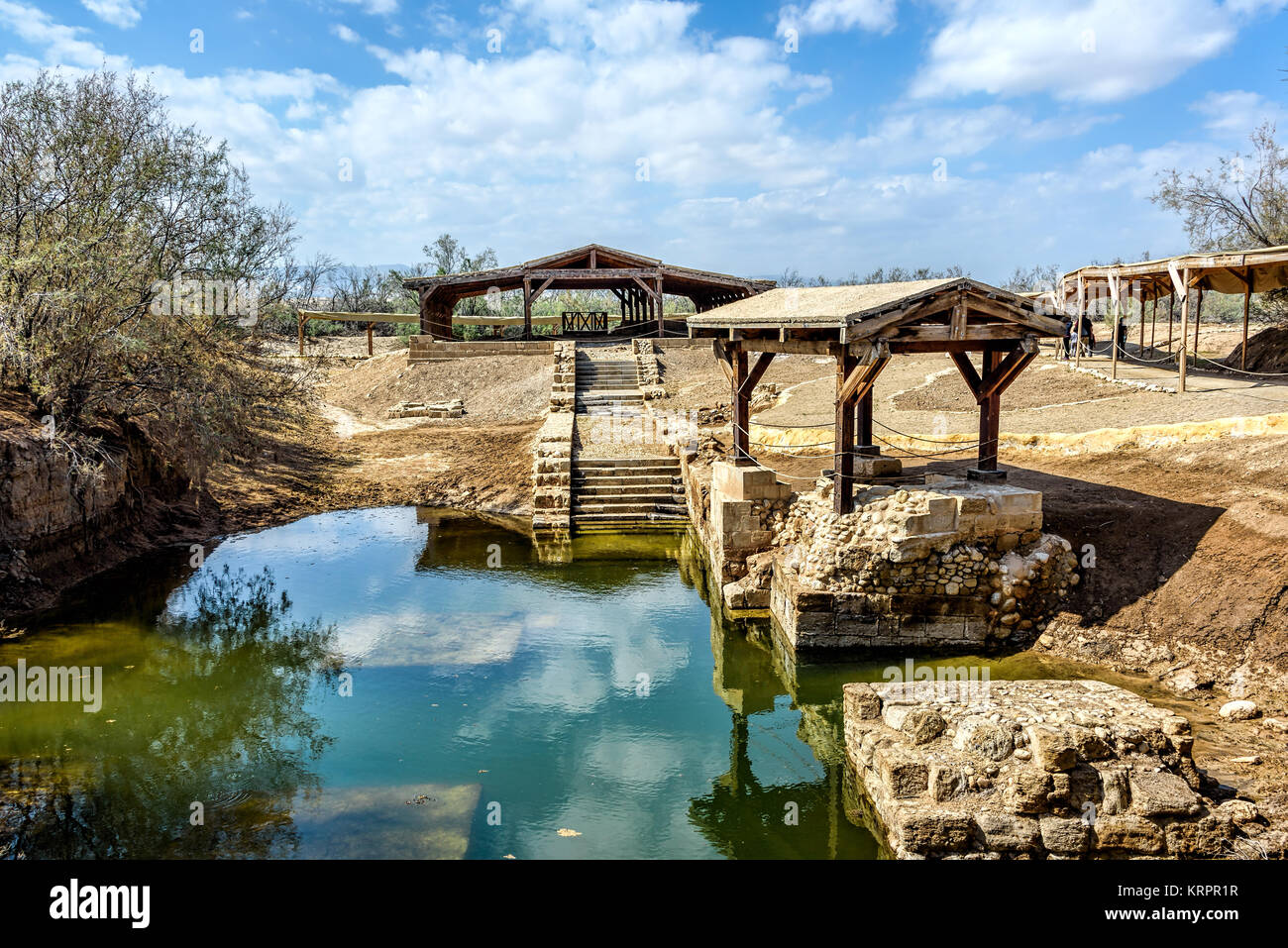 Authentic site of Jesus' baptism under blue skies with fluffy clouds - Stock Image