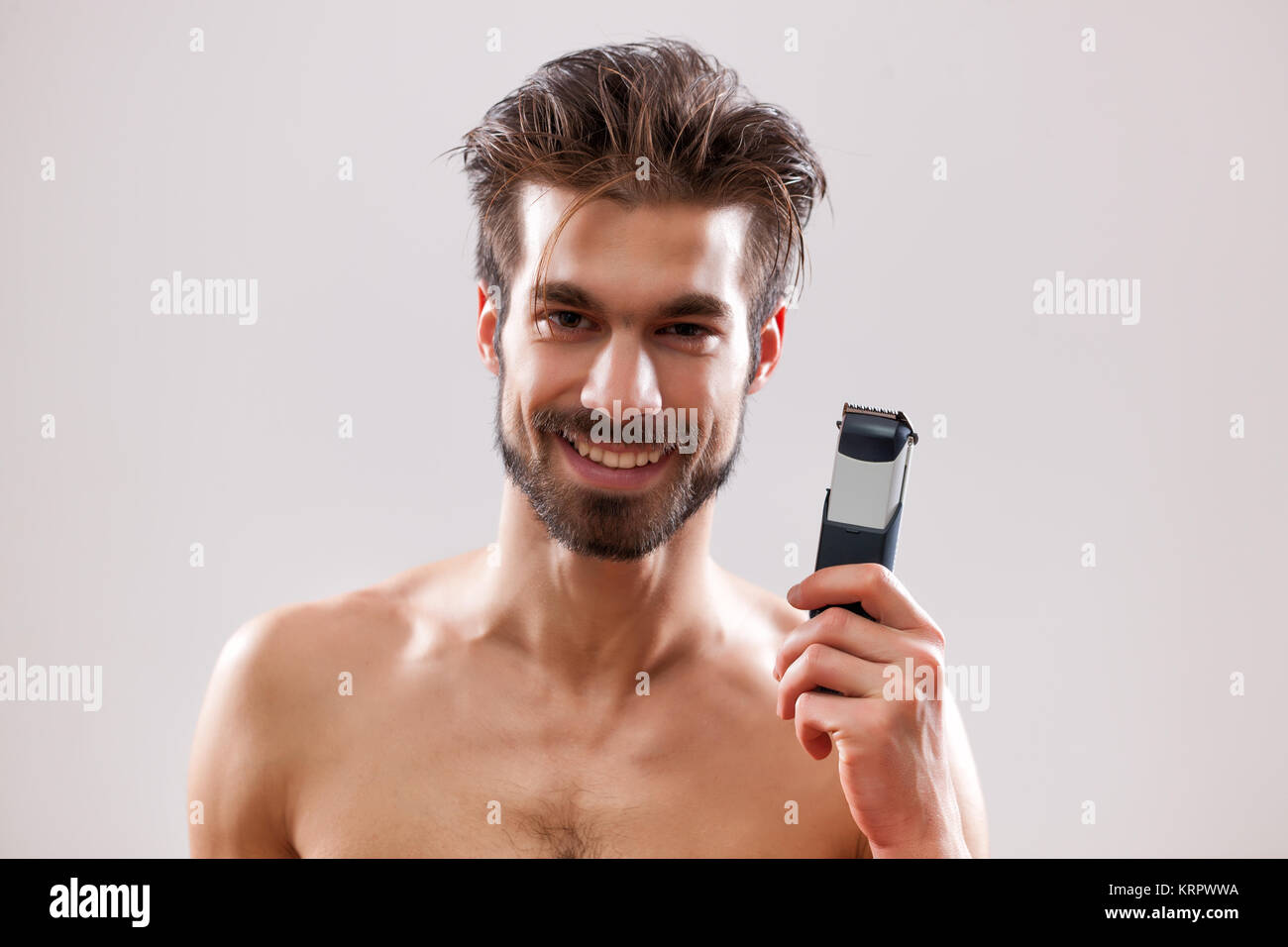 Young man is holding electric razor and he is going to shave his beard. - Stock Image