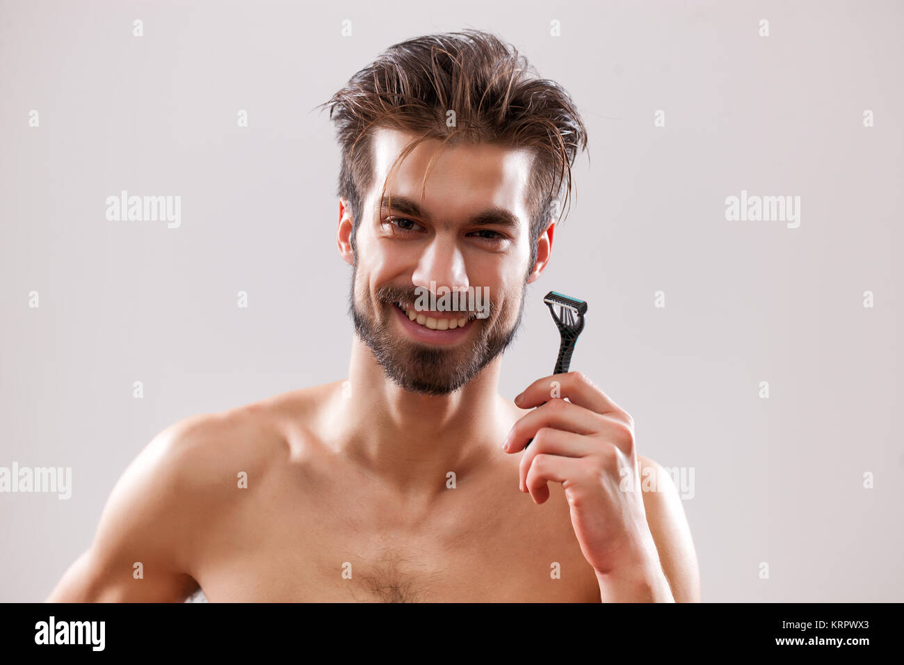 Young man is holding razor and he is going to shave his beard. - Stock Image