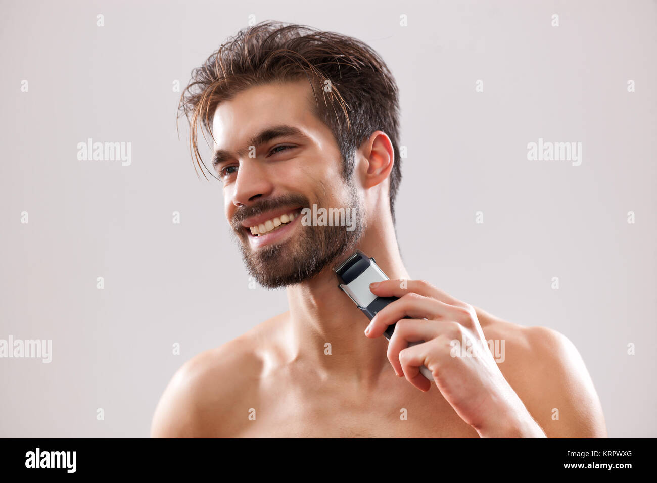 Young man is shaving his beard with electric razor. - Stock Image