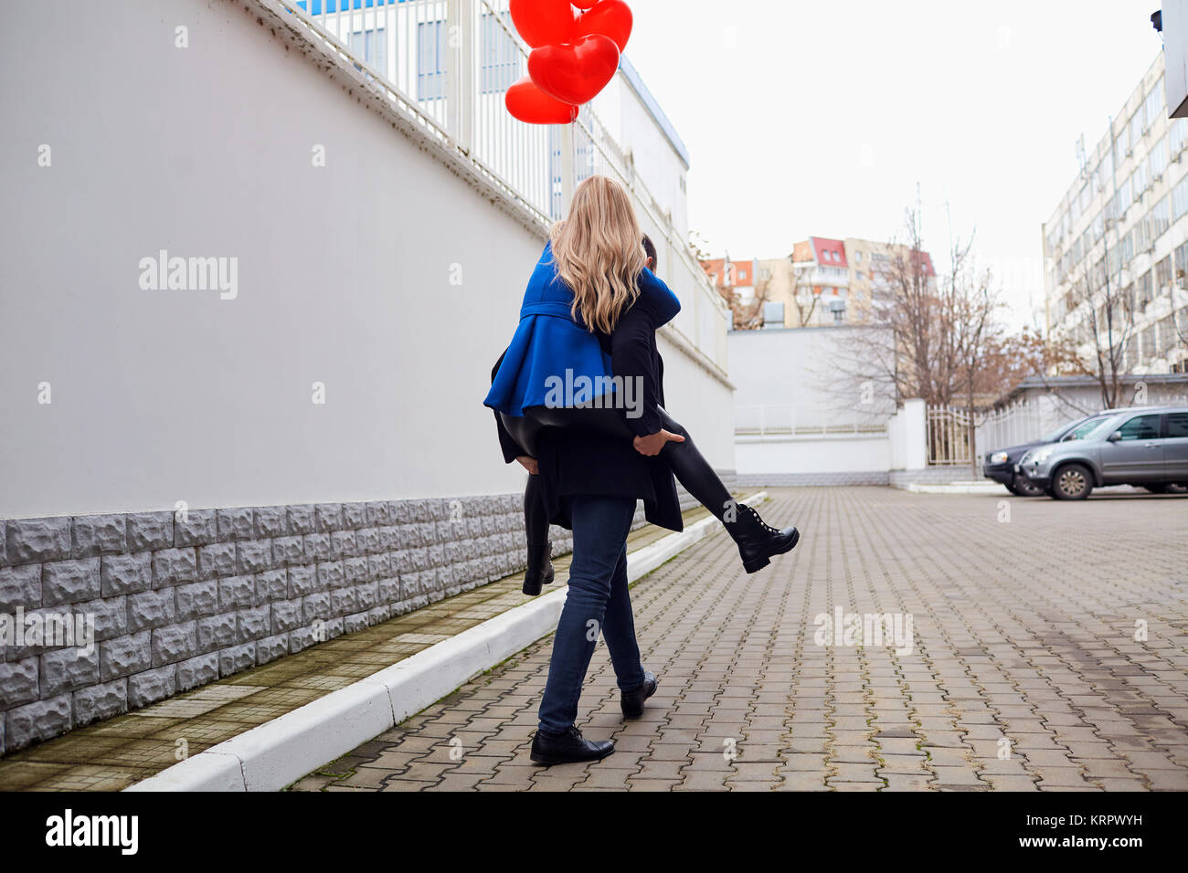 Girl piggyback on guy with red heart balloons on the street.  - Stock Image