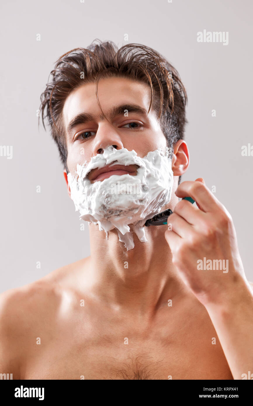 Young handsome man is shaving his beard. - Stock Image