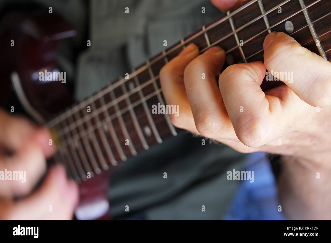 Closeup on musician's hand forming a chord on an electric guitar. Stock Photo