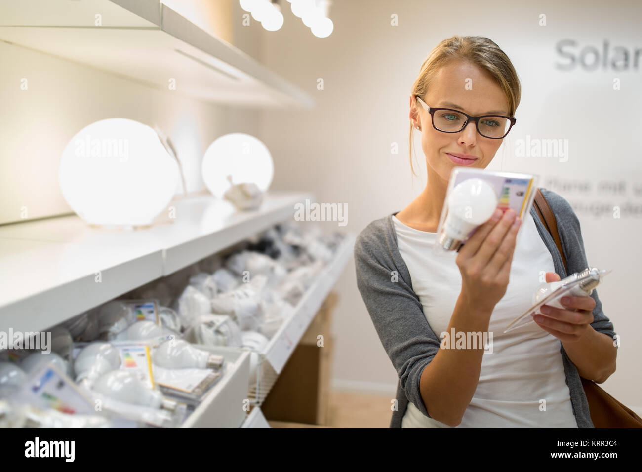 Energy efficient lighting choice: Pretty, young woman holding and choosing a LED diode light bulb for her lamp in - Stock Image