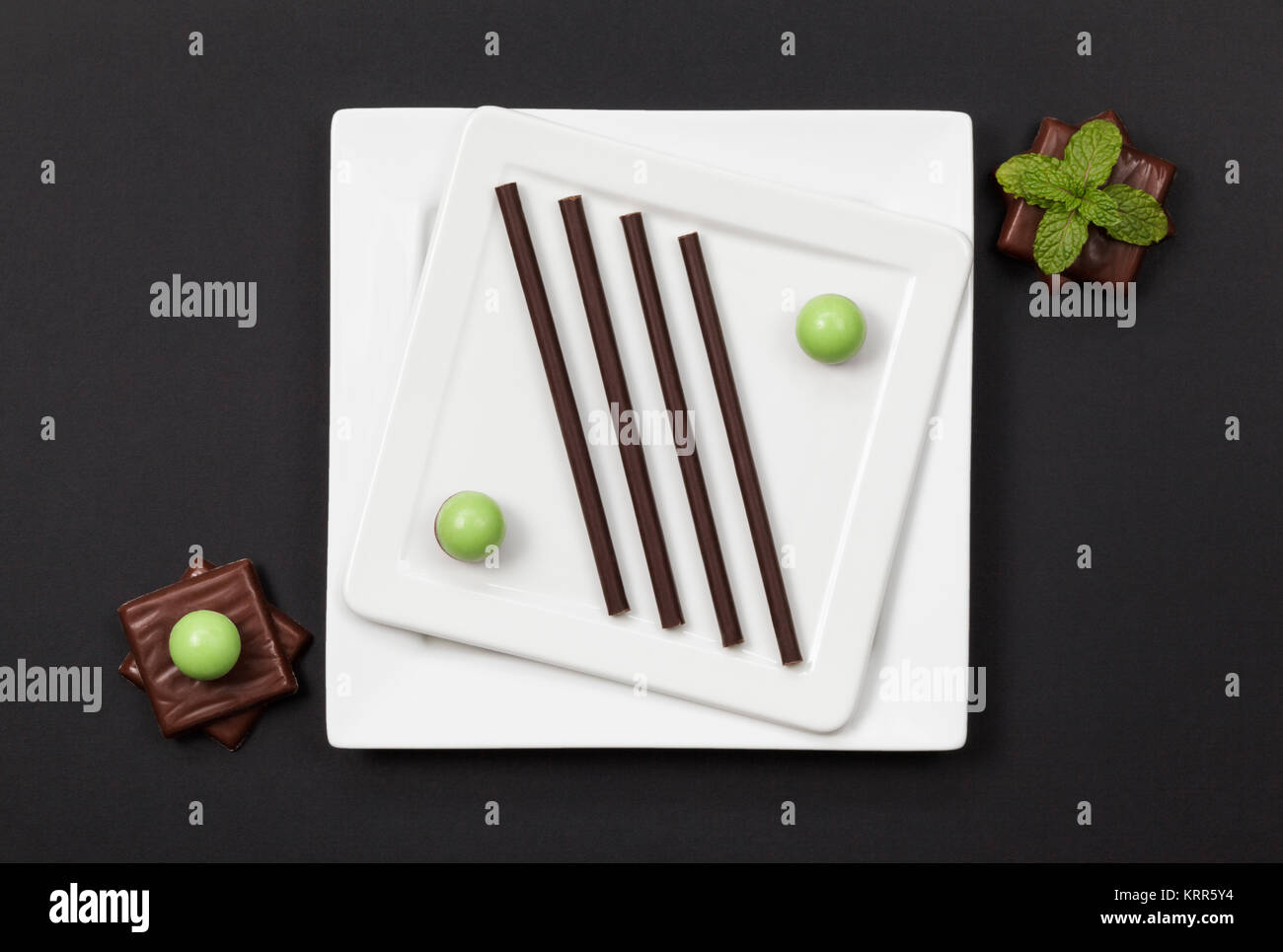 an assortment of Mint Chocolates and two white plates - Stock Image