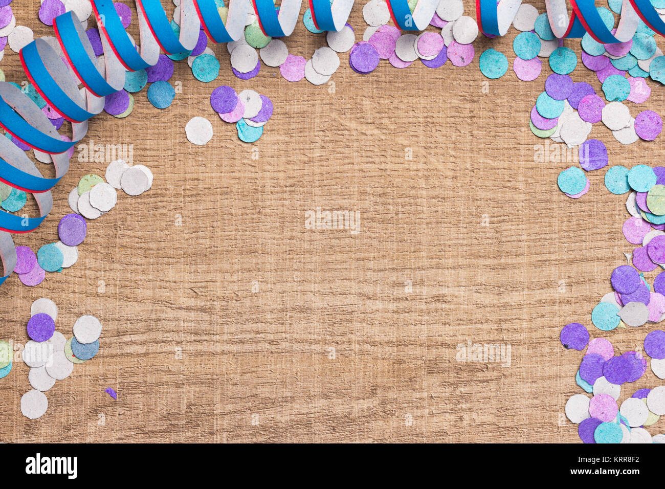 Colorful confetti and streaming spread over wooden table. Cool colors: blue, purple and aqua. Carnaval. - Stock Image