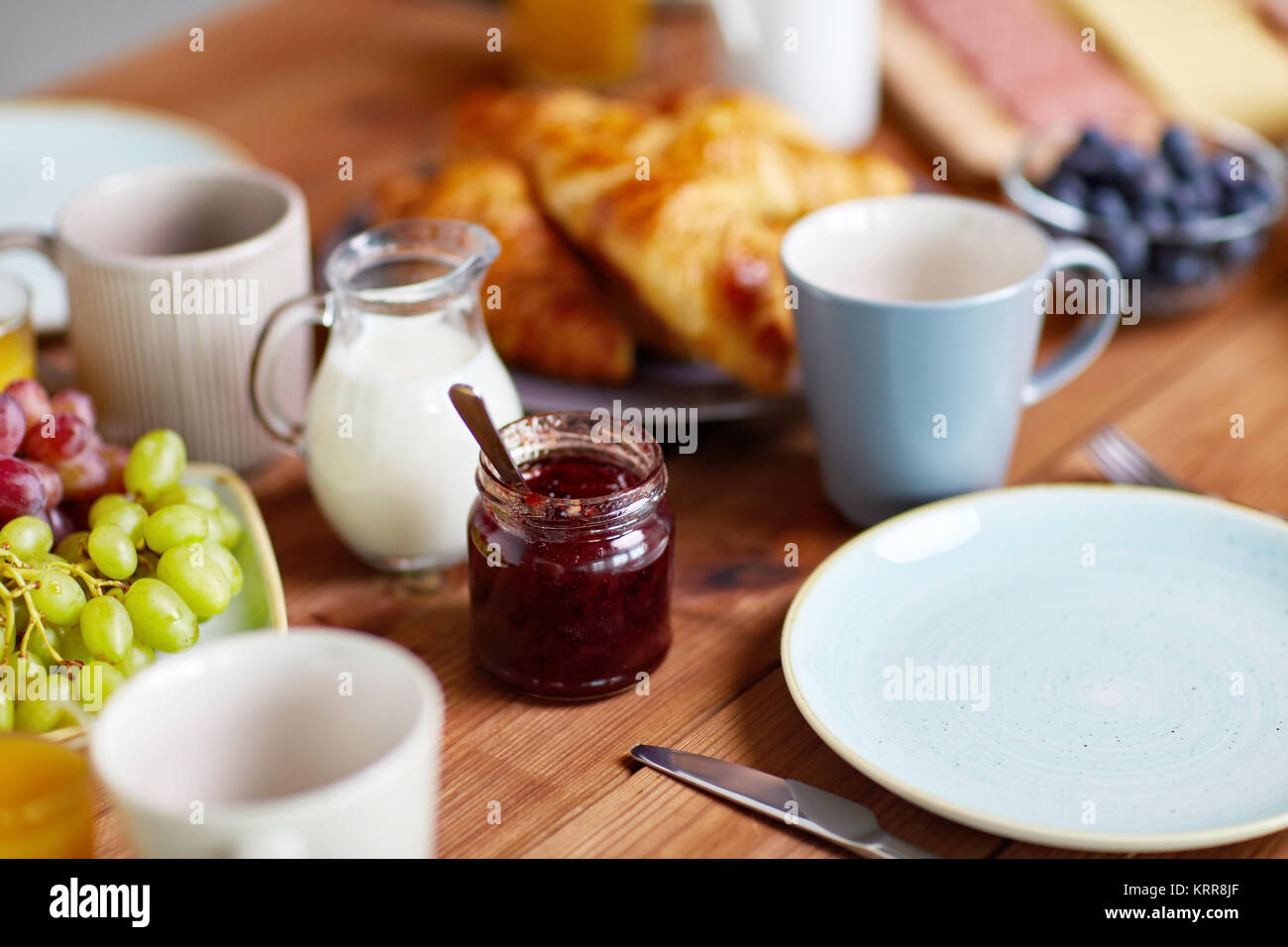 jar with jam on wooden table at breakfast - Stock Image