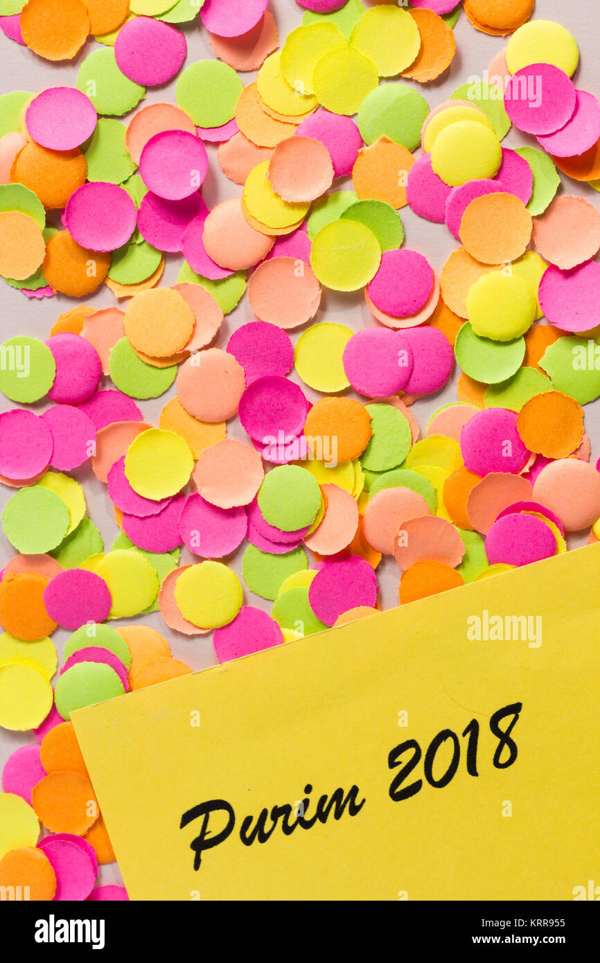 Colorful confetti spread over table. Warm colors: pink, yellow and orange. Purim celebration, Jewish tradition. - Stock Image