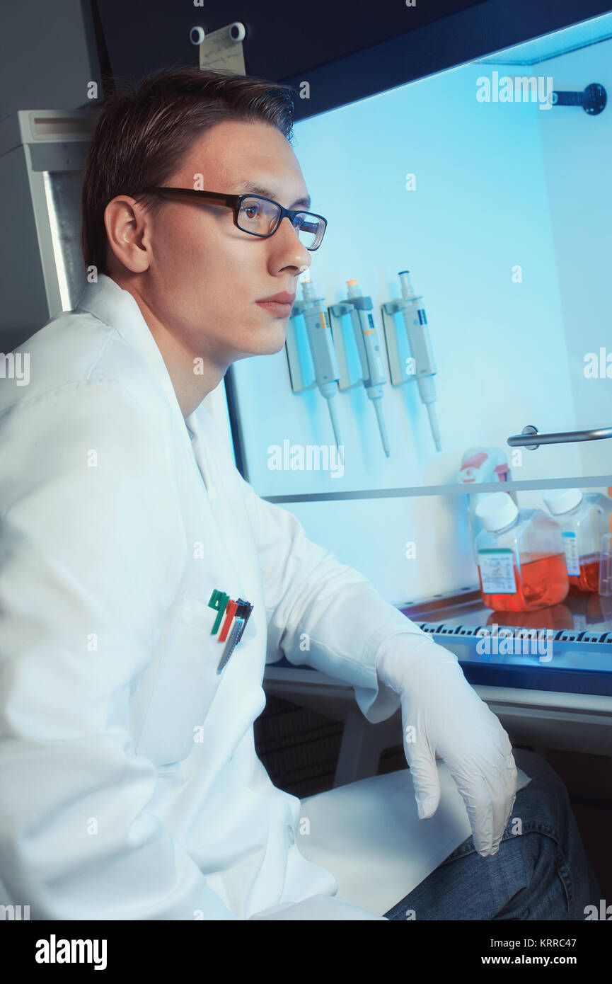 Young male scientist, graduate student or tech sitting by the cell culture hood, half body, focus on the eyes - Stock Image