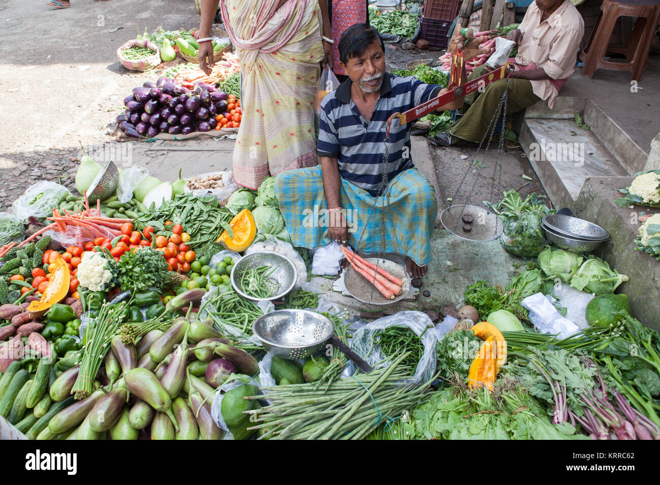 Vegetable seller using scales to weigh carrots in the Garia district of Kolkata, India - Stock Image