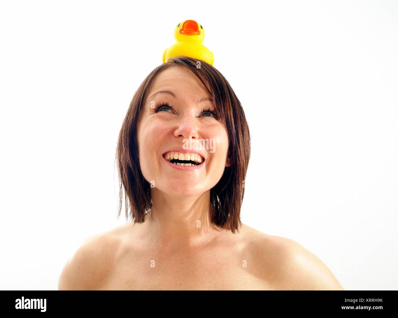 Junge, lachende Frau mit Badeente am Kopf - young, laughing woman with rubber duck on head Stock Photo