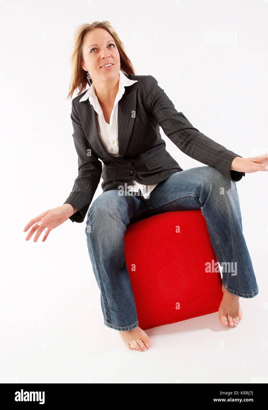Blonde Frau, 25+,  sitzt auf einem roten Stoffwuerfel - young, blond woman in portrait - Stock Image