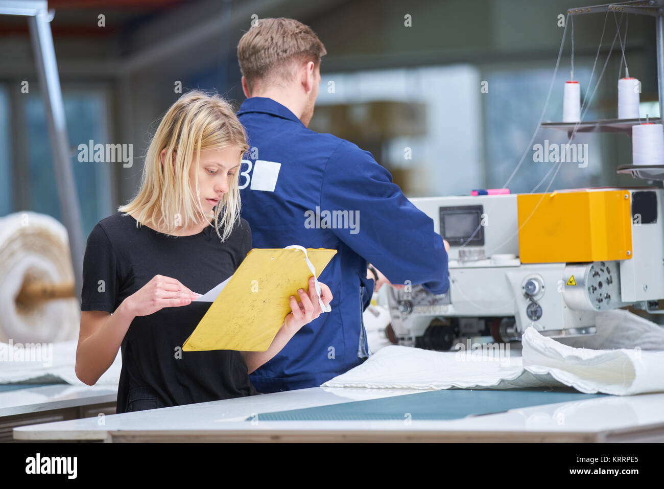 Seamstress is new assigned to a machine in a textile factory, the foreman explains something - Stock Image
