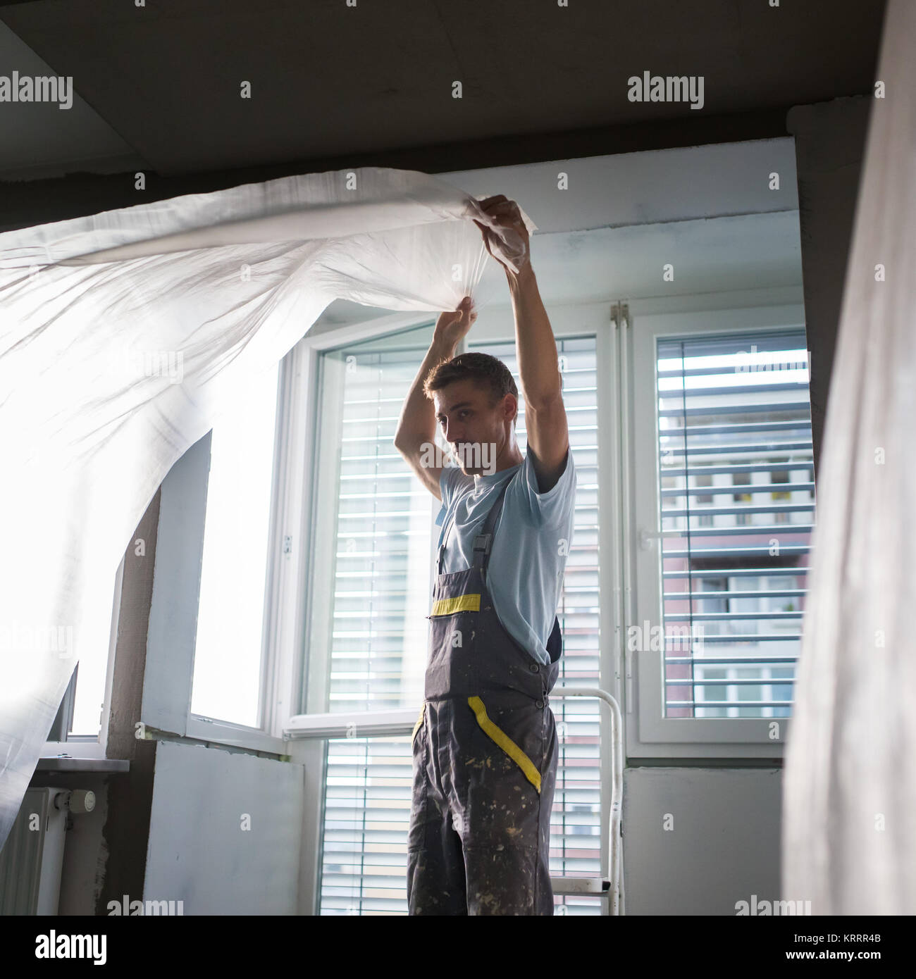 Plasterer renovating indoor walls and ceilings. Finishing works. - Stock Image