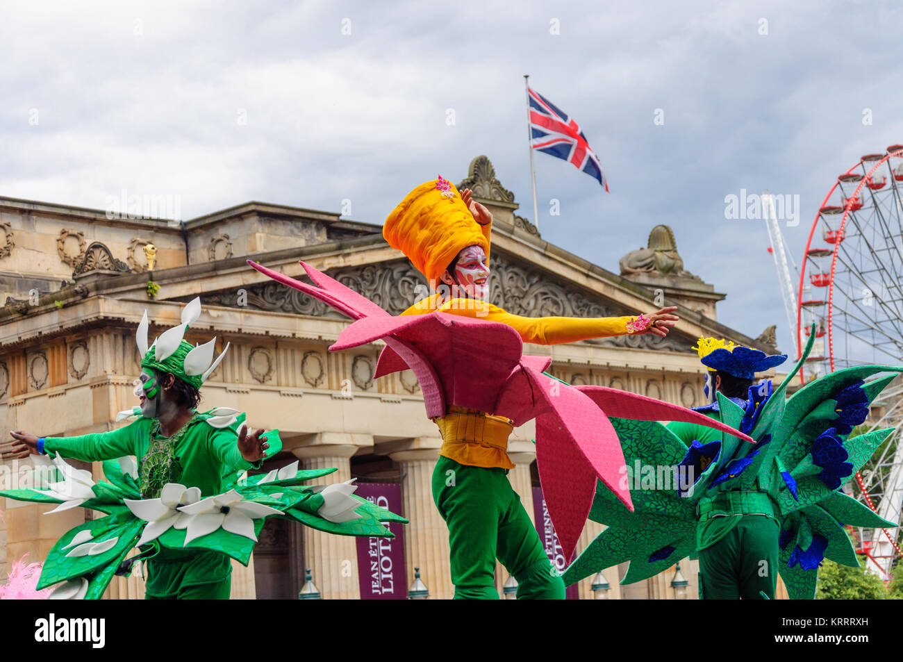 Stilt walker wearing a flower costume performing in the Carnival of The Edinburgh Jazz and Blues Festival travelling - Stock Image