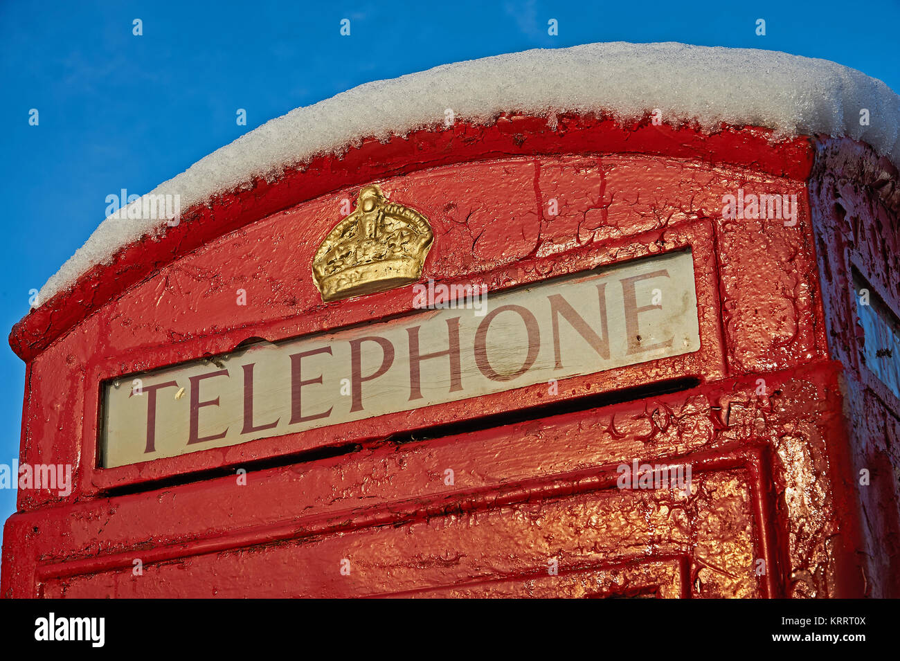 Iconic red telephone box against a blue sky, with a top cover of fresh snow - Stock Image