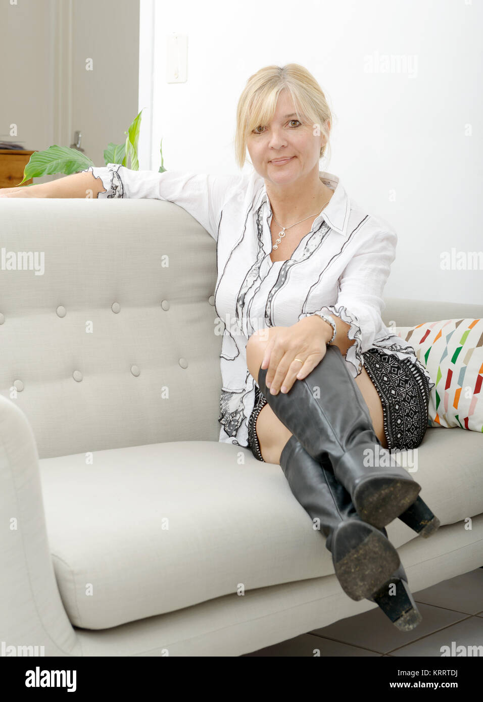 blond mature woman relaxing in sofa