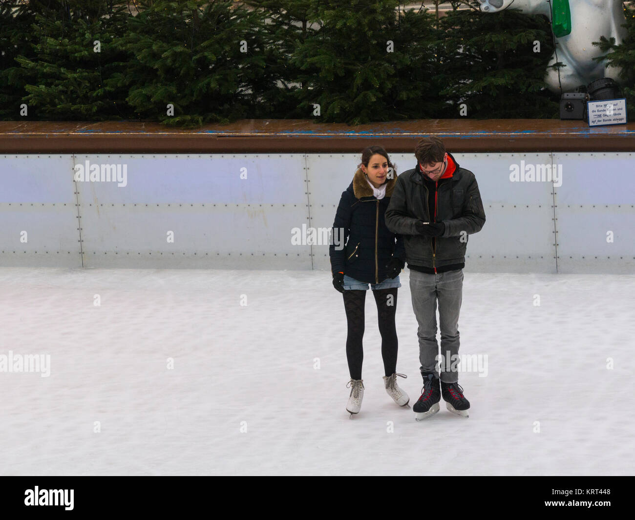Young Couple standing on ice skates Münchener EisZauber Munich Ice Magic ice rink man checking Iphone for messages - Stock Image