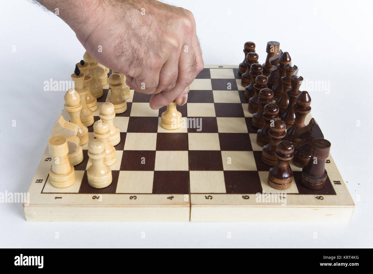 Chess. The man's hand makes the first move E2-E4. - Stock Image