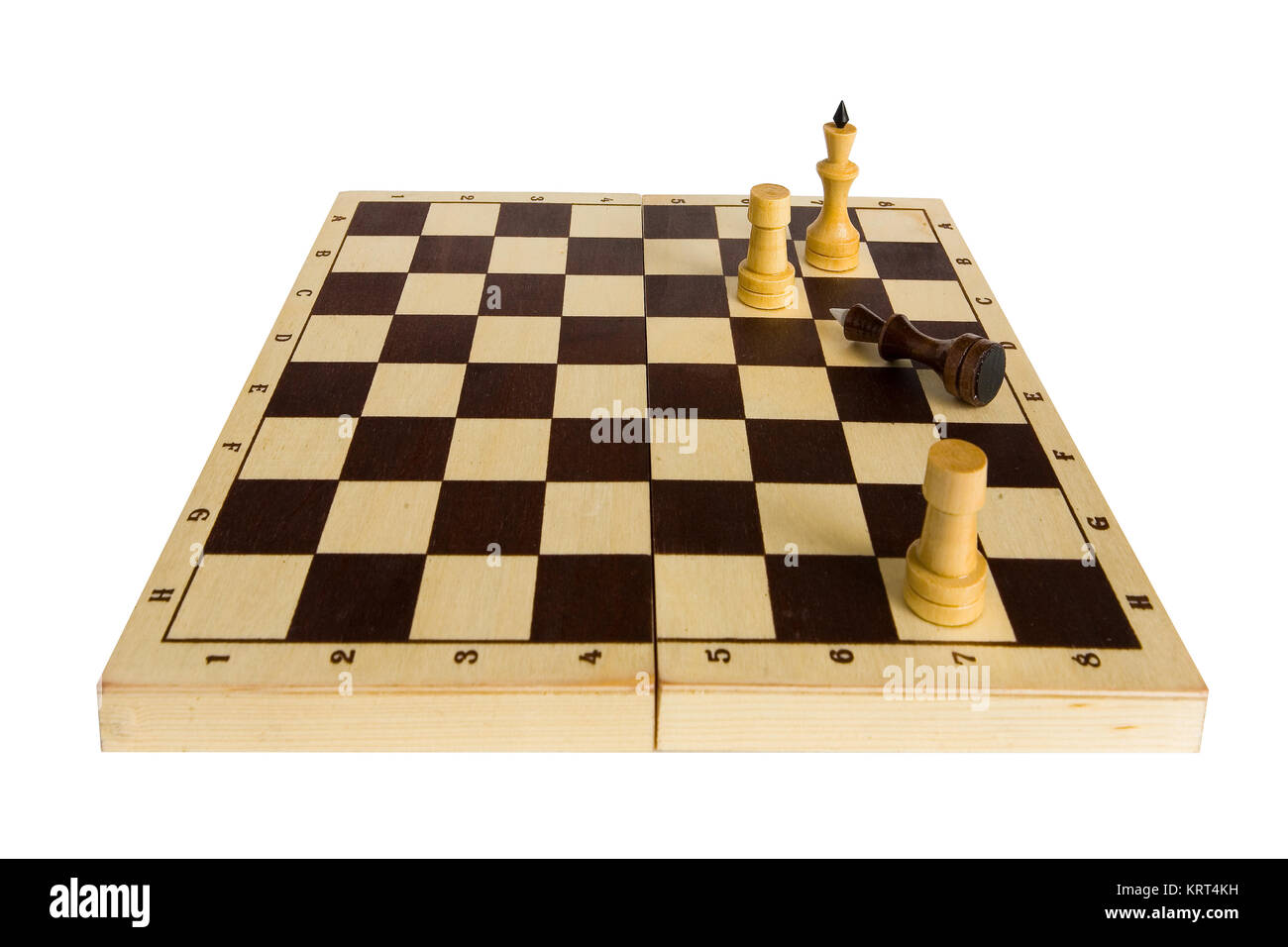Chess. The Black King gave in and lies on the chessboard. - Stock Image