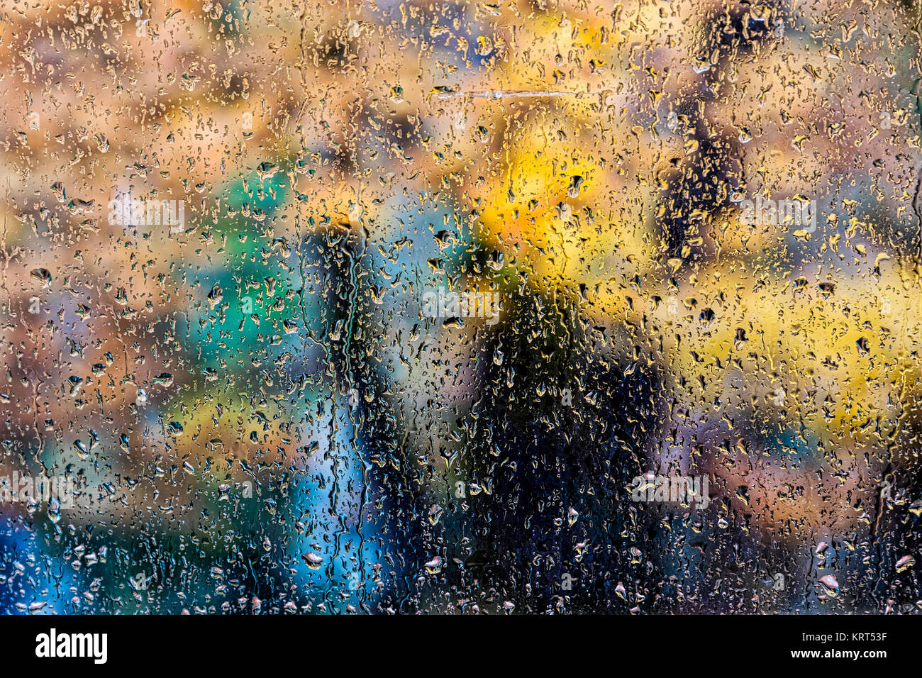 rain in the park glass wet surface with reflection, rain drops on the drenched window glass, background window in - Stock Image