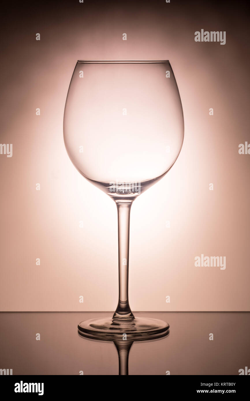 One empty wineglass for red wine on diffusion lit background, advertizing shot for restaurant, winemaking - Stock Image