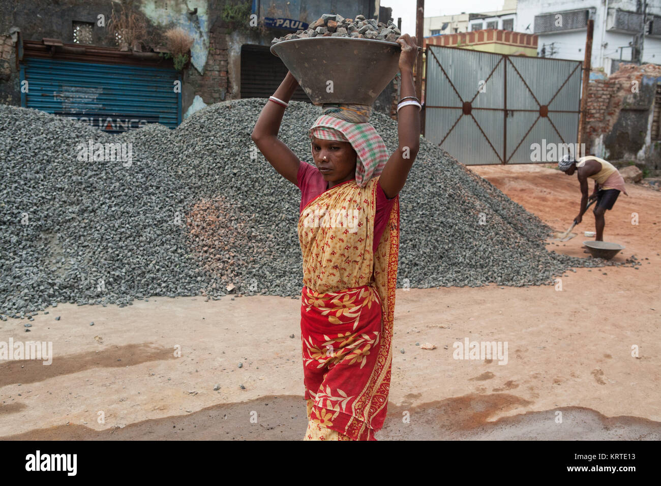 A women carrying a tray of stone chippings on a building site in Asansol, India - Stock Image