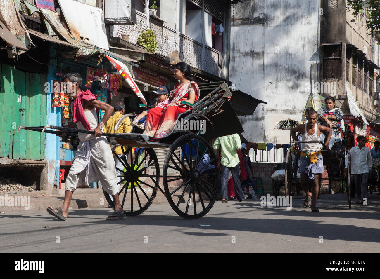 A hand-pulled rickshaw carrys passengers through the streets of Kolkata, India - Stock Image