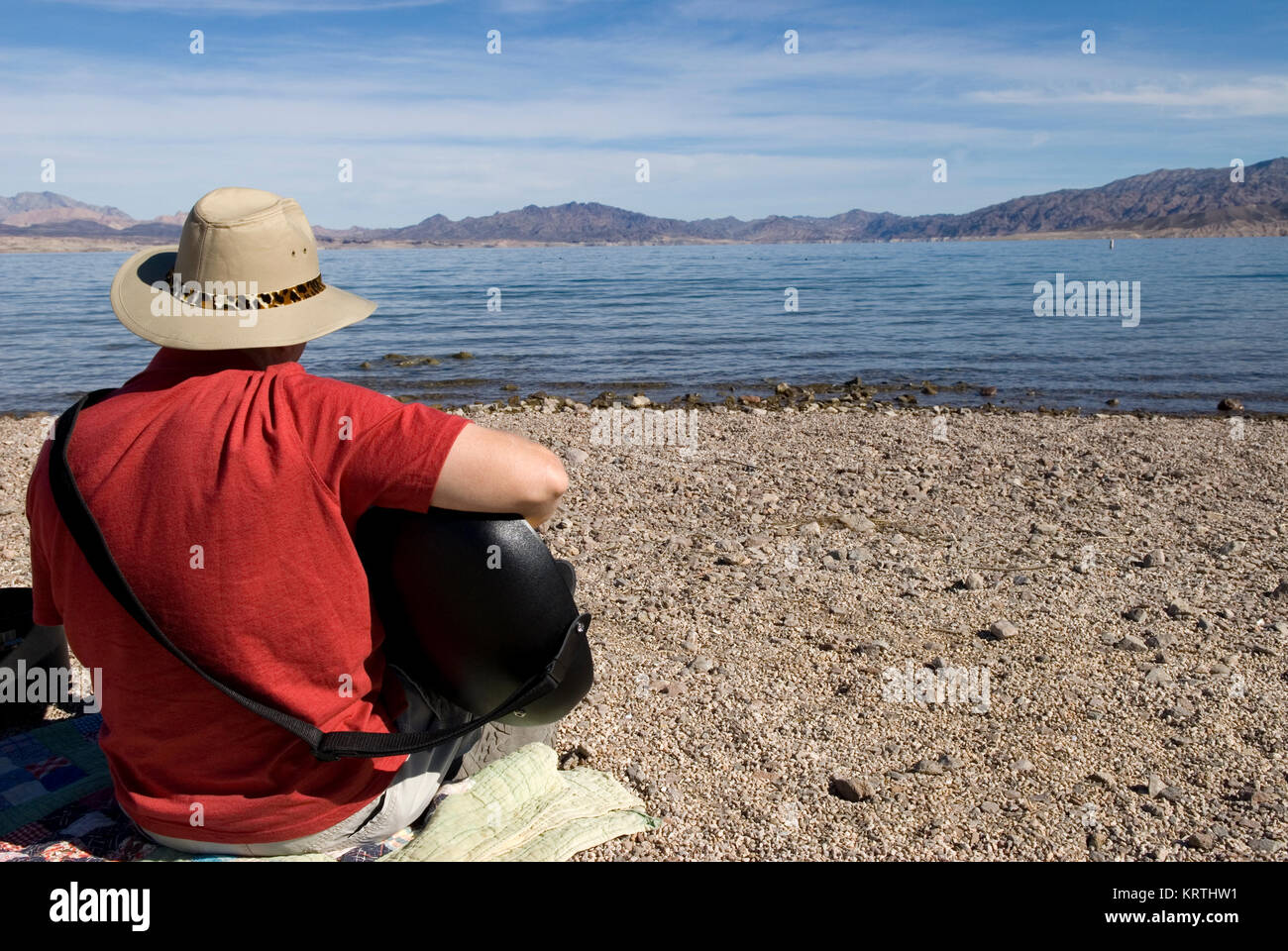 Man plays guitar on beach at Lake Mead National Recreation Area Nevada, USA. Stock Photo