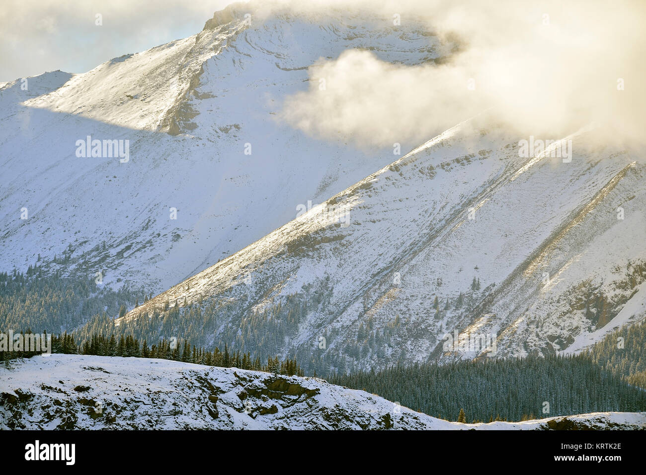 A close up landscape of therocky mountains in Alberta Canada with warm tone golden light shining on the fresh snow. - Stock Image