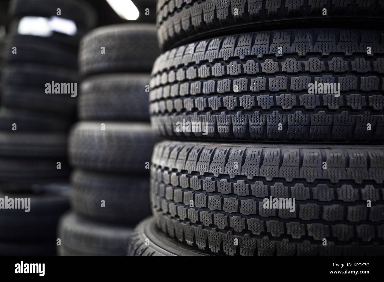 Tires for sale at a tire store - stacks of old used tires Stock Photo