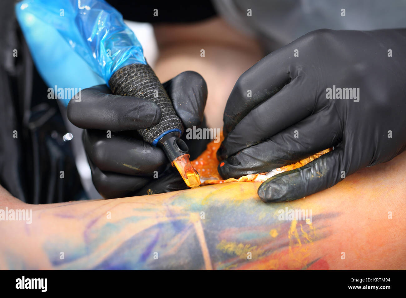 tattoo,tattoo artist does the tattoo on the man's hand. Stock Photo
