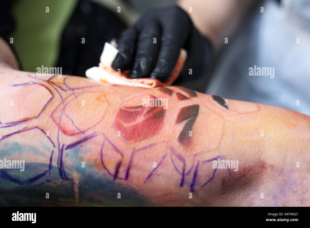 creating a tattoo in a tattoo parlor. Stock Photo