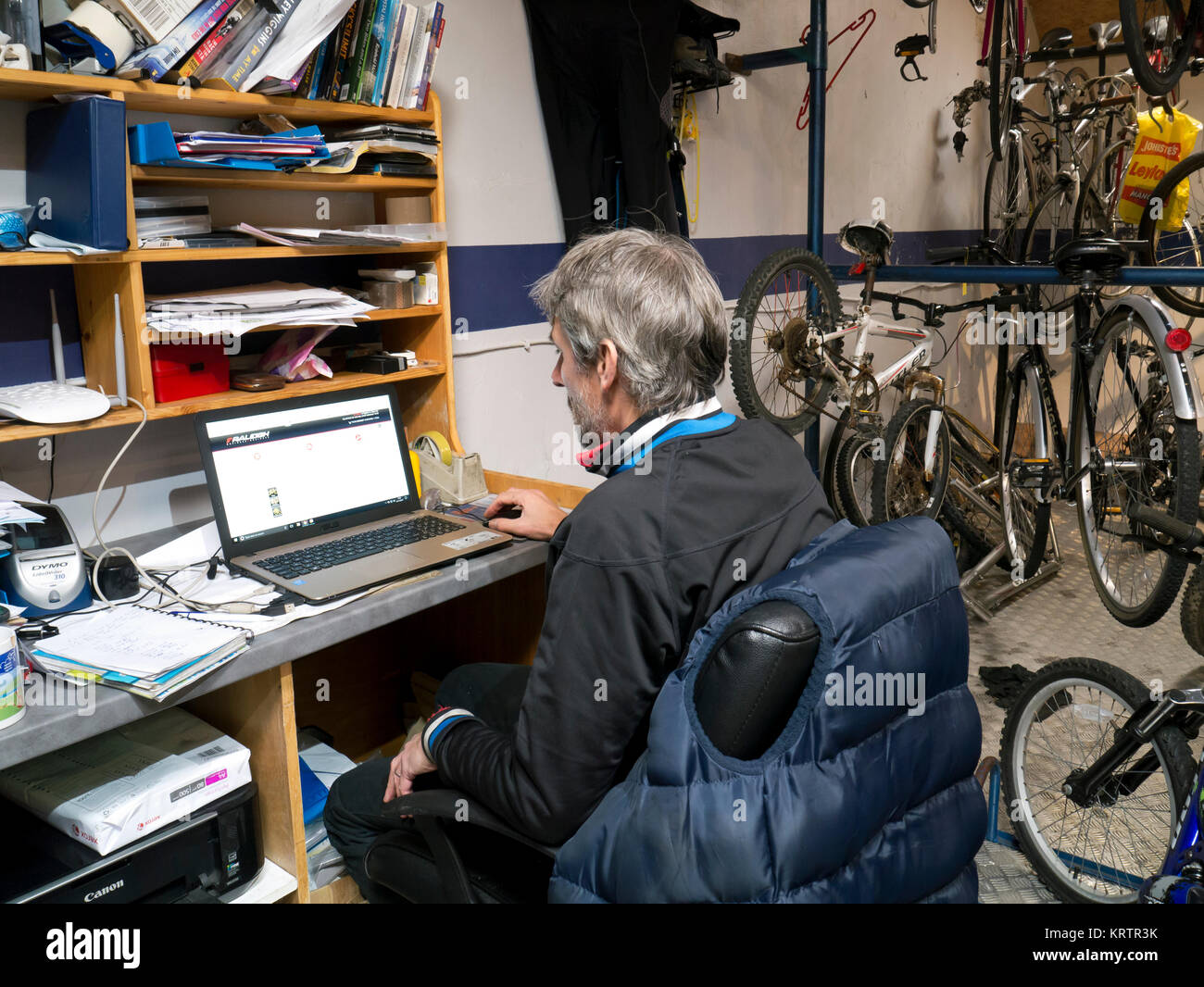 Self employed man working on a laptop - Stock Image
