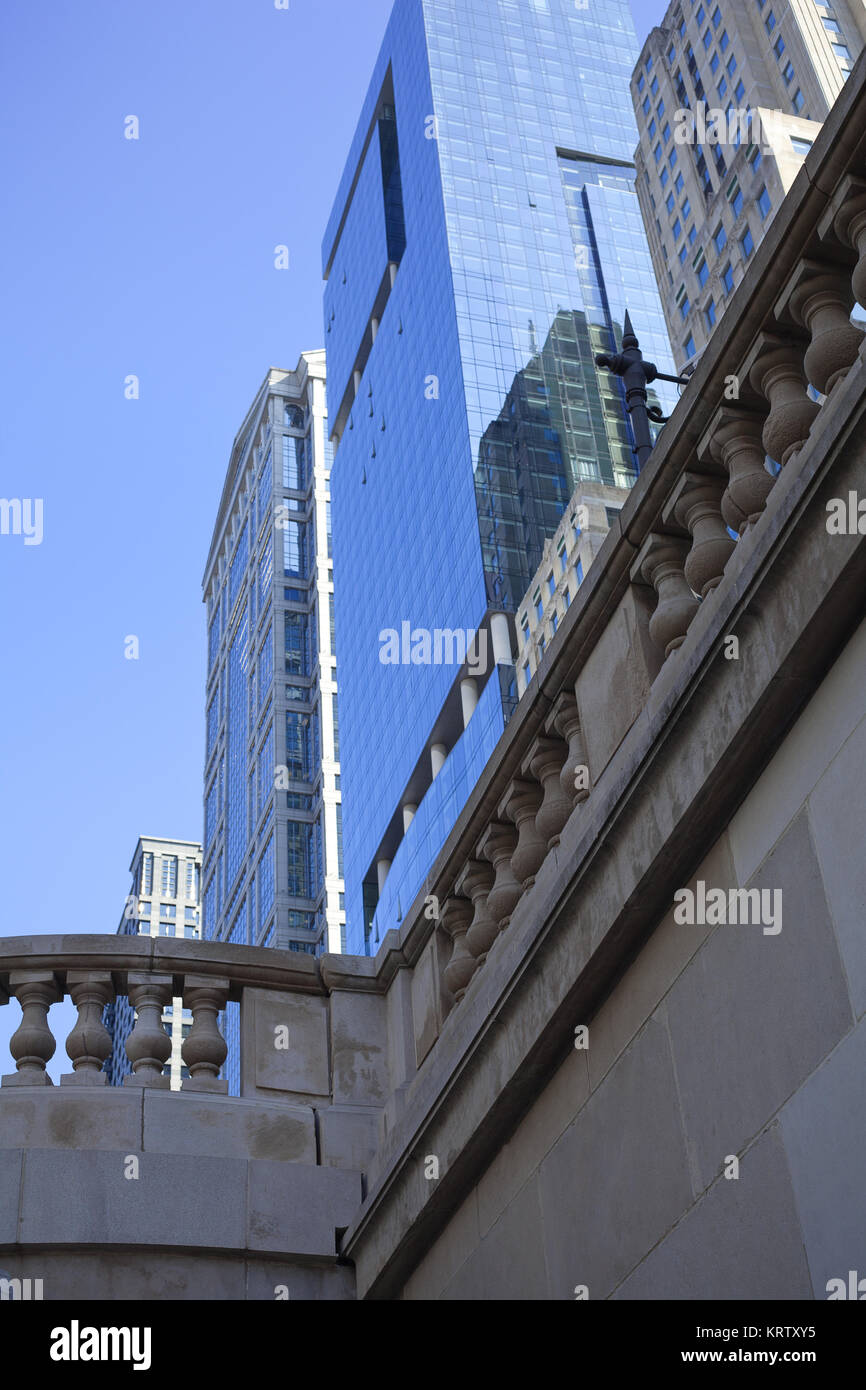 Skyscrapers seen above and behind classic stone pillars - Stock Image