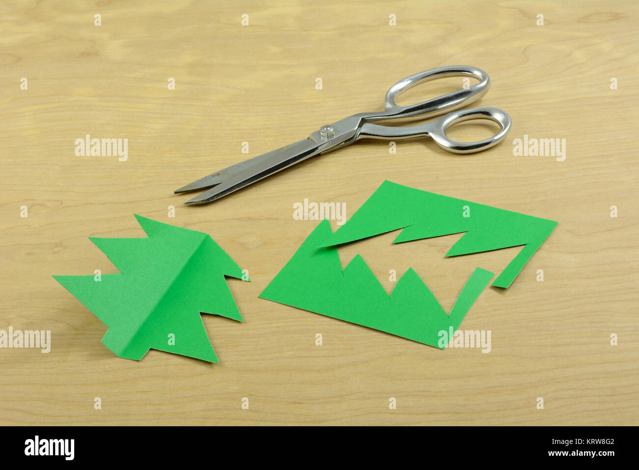 Stainless steel scissors and Christmas tree cut from construction paper on wooden table - Stock Image