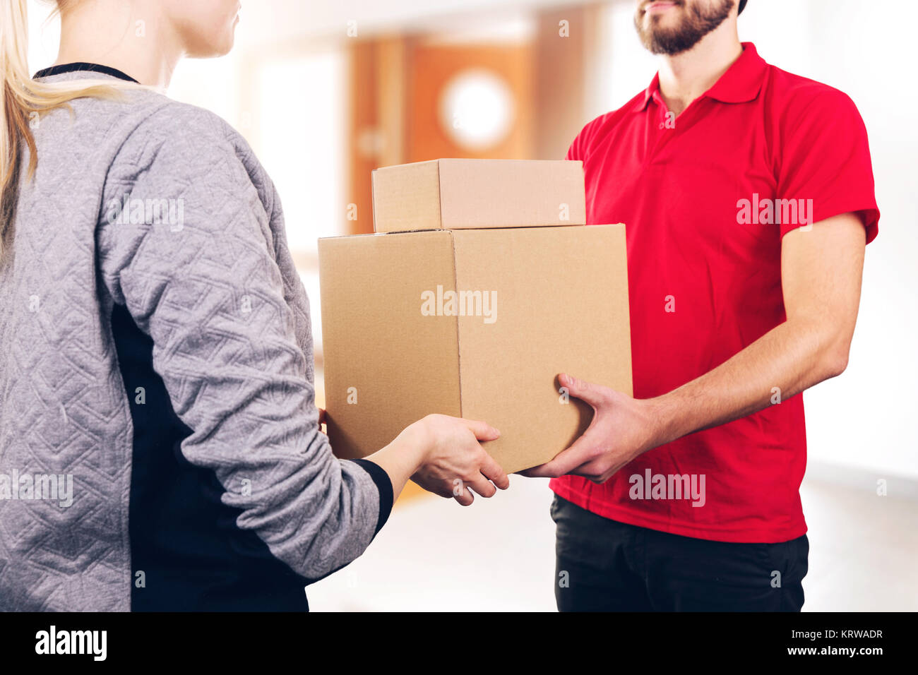woman accepting a delivery of boxes from delivery service courier - Stock Image
