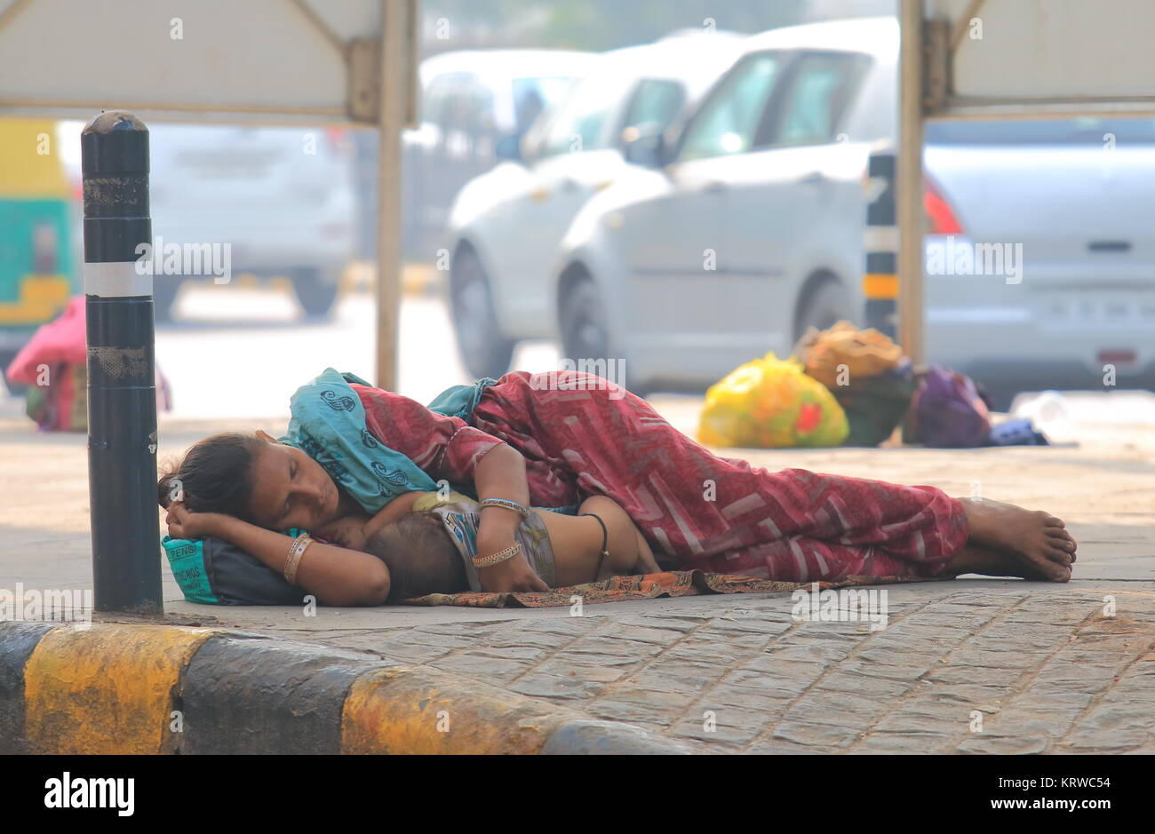 Indian woman cuddle a baby and sleep on the street in downtown New Delhi India - Stock Image