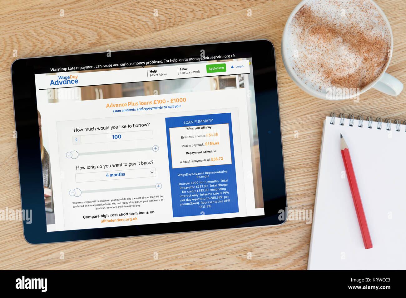 The Wage Day Advance website on an iPad tablet device which rests on a wooden table beside a notepad and pencil - Stock Image