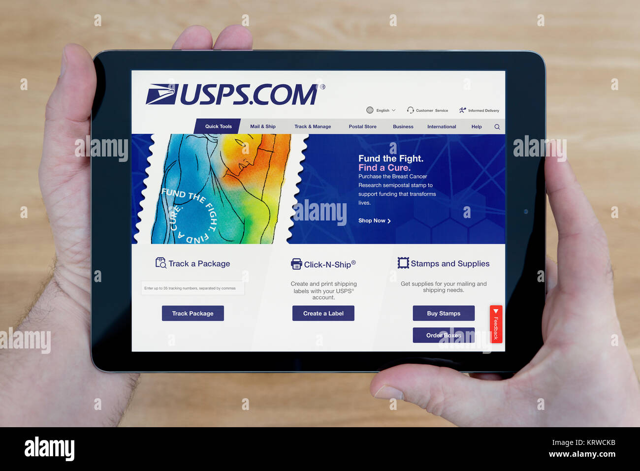 A man looks at the United States Postal Service website (USPS.com) on an iPad tablet, shot against a wooden table - Stock Image