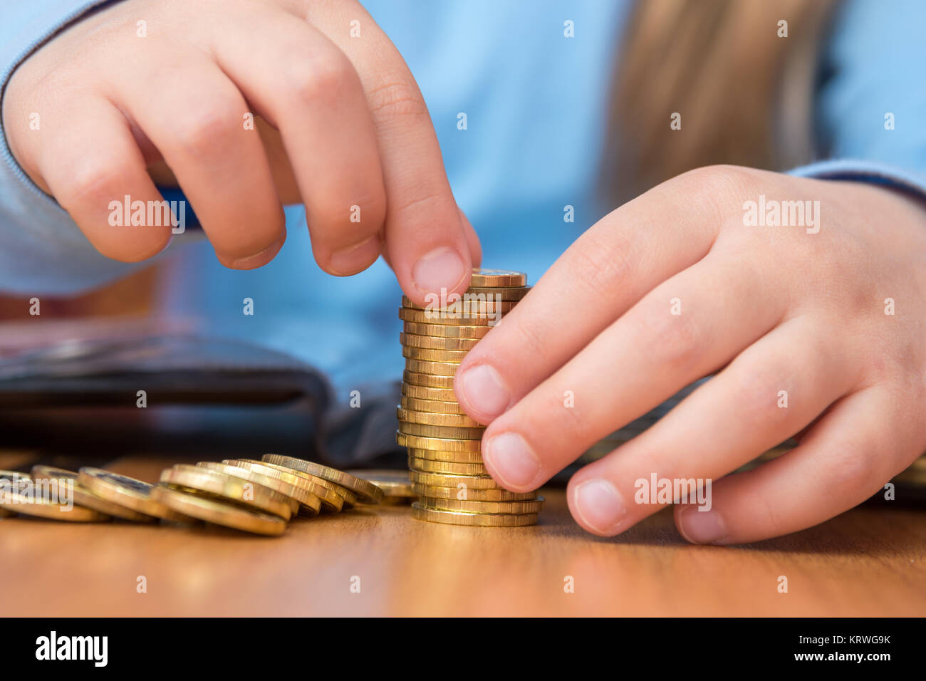 Child collects a stack of golden coins, close-up - Stock Image
