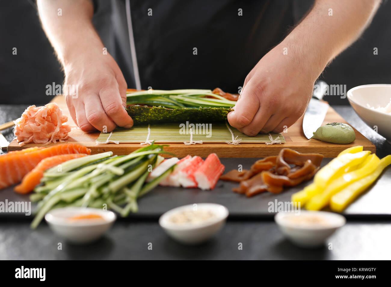 Mata bambusowa, przygotowywanie sushi. Jak przygotować sushi. Skręcanie rolki sushi w matę bambusową - Stock Image