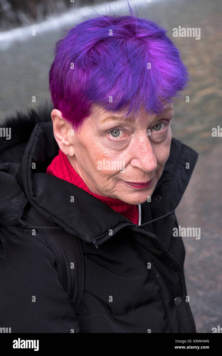 Posed portrait of an attractive woman in her very early sixties with youthful purple and red hair. In Midtown Manhattan, - Stock Image