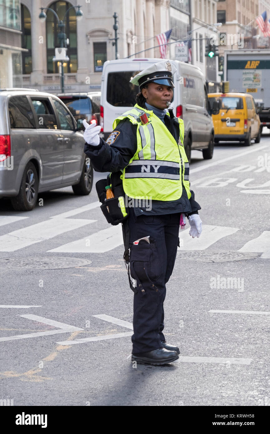 A policewoman directing traffic on Fifth Avenue and 43rd Street in Midtown Manhattan, New York City. - Stock Image