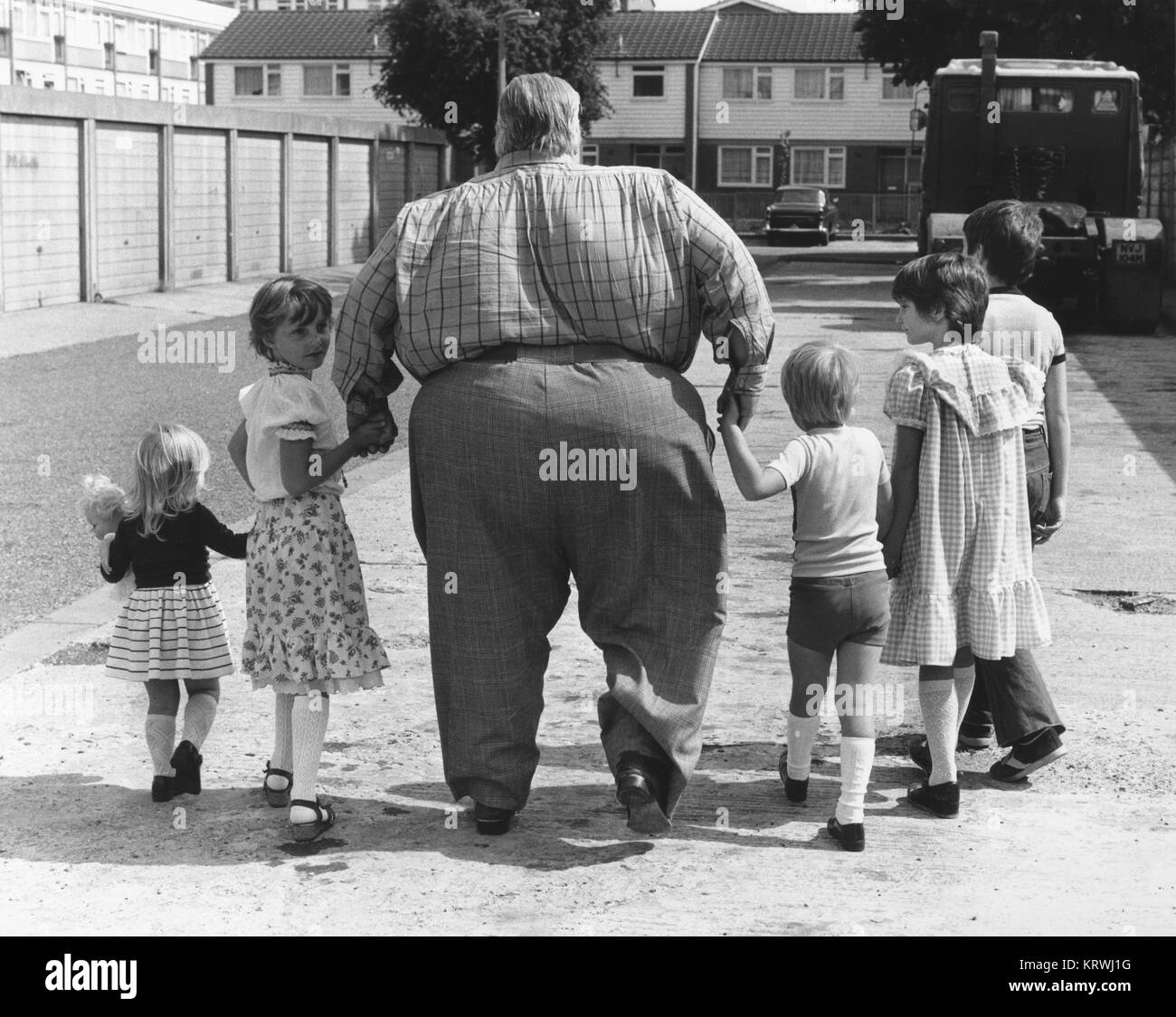 Big man with children, England, Great Britain - Stock Image