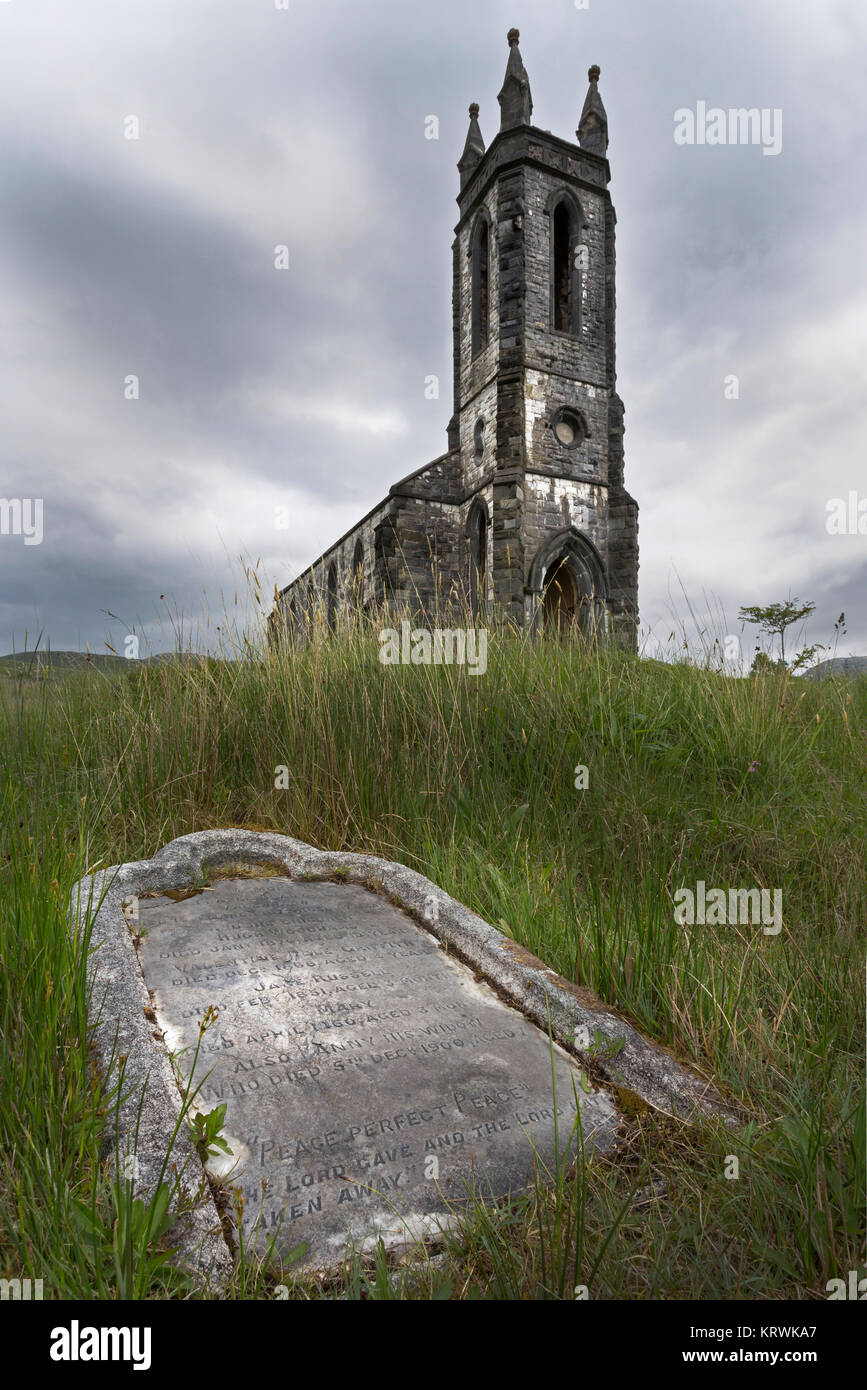 Old tombstone with decayed church in the background, Dunlewy, County Donegal, Ireland - Stock Image