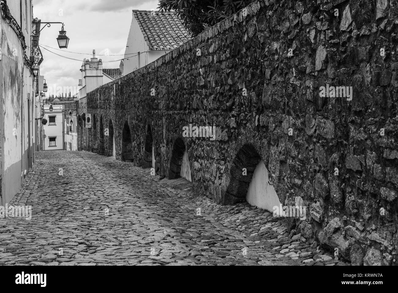 Street in the old town of Evora (Portugal), with the archaeological remains of a Roman aqueduct. - Stock Image